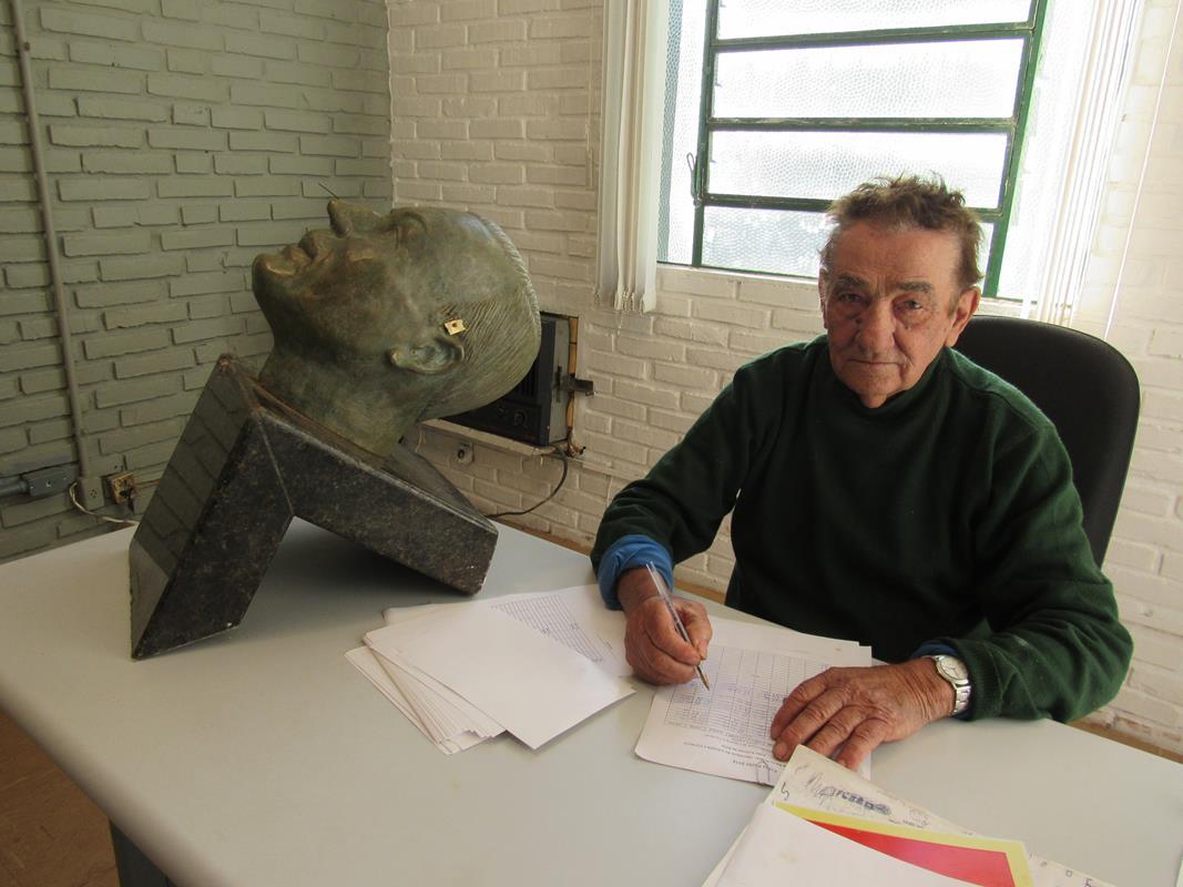 Monumento a Adão Felippe Pippi está desmontado. Na foto, o Servidor público Adão Antunes assina o ponto ao lado da cabeça do homenageado que foi alvo de vandalismo