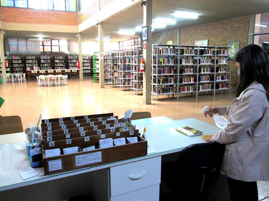 Bibliotecária Fernanda Ribeiro Paz higieniza livros no momento da entrega